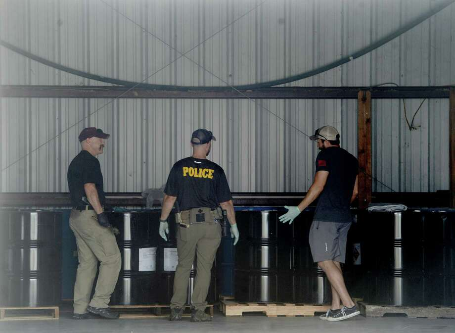 Members of the DEA, ATF, and other law enforcement agencies investigate, preparing to test the contents of barrels inside a warehouse, during a raid at Jake's Fireworks Super Store and surrounding warehouses Wednesday in Nederland. Several employees were detained inside as the raid continued before eventually being released. One man was handcuffed and taken into custody.  Photo taken Wednesday, July 15, 2020 Kim Brent/The Enterprise Photo: Kim Brent / The Enterprise / BEN