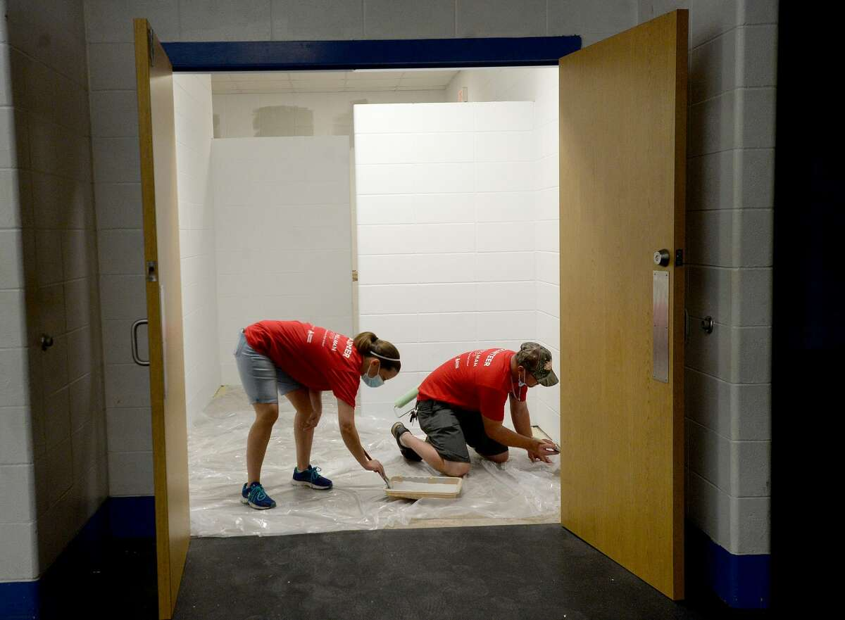 Ashley and Eric Davis join in the volunteer effort to repaint the locker rooms as the renovations led by Hollman, Inc., following this year's contest win, continue at Hamshire - Fannett High School Friday. Photo taken Friday, July 17, 2020 Kim Brent/The Enterprise