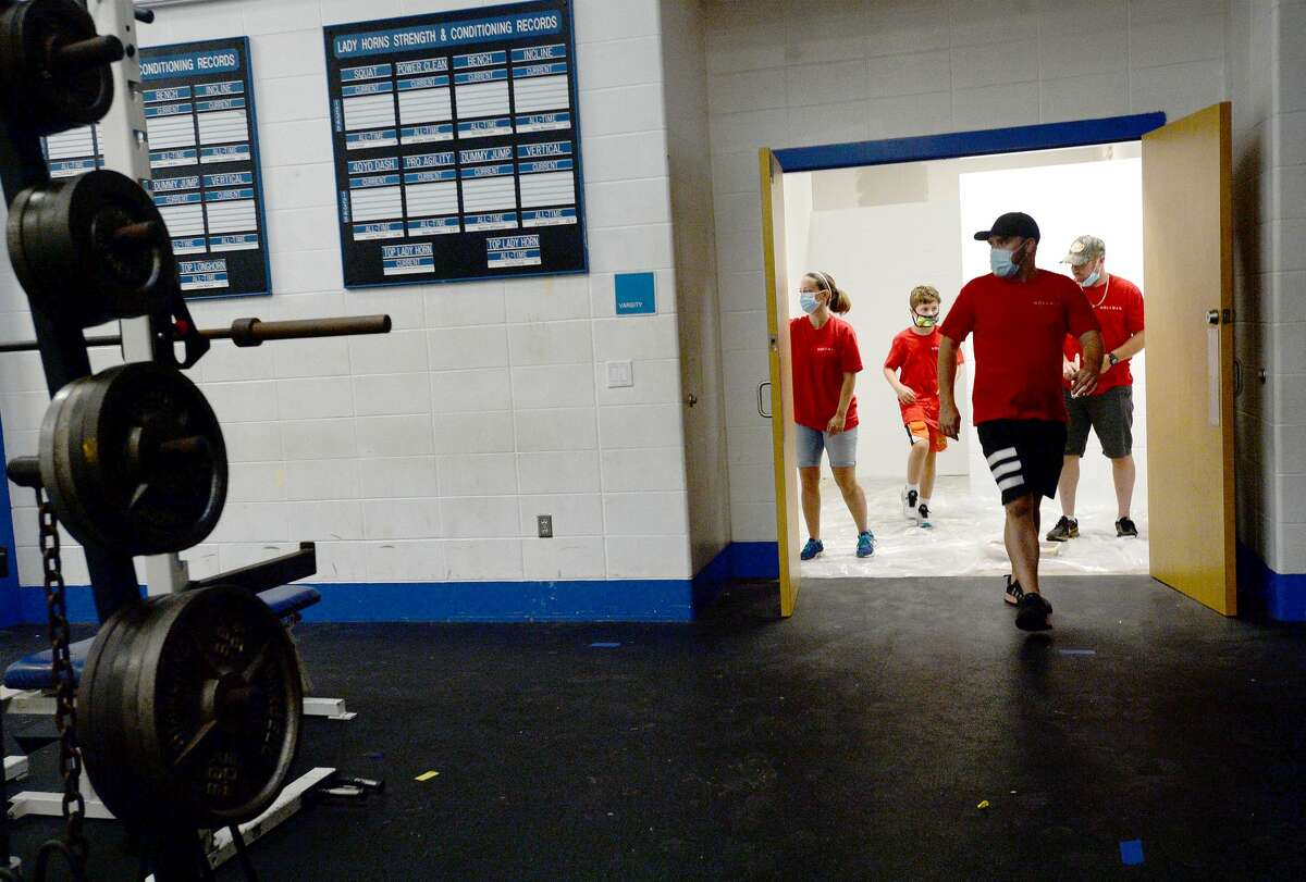 Volunteers join in the effort to repaint the locker rooms as the renovations led by Hollman, Inc., following this year's contest win, continue at Hamshire - Fannett High School Friday. Photo taken Friday, July 17, 2020 Kim Brent/The Enterprise