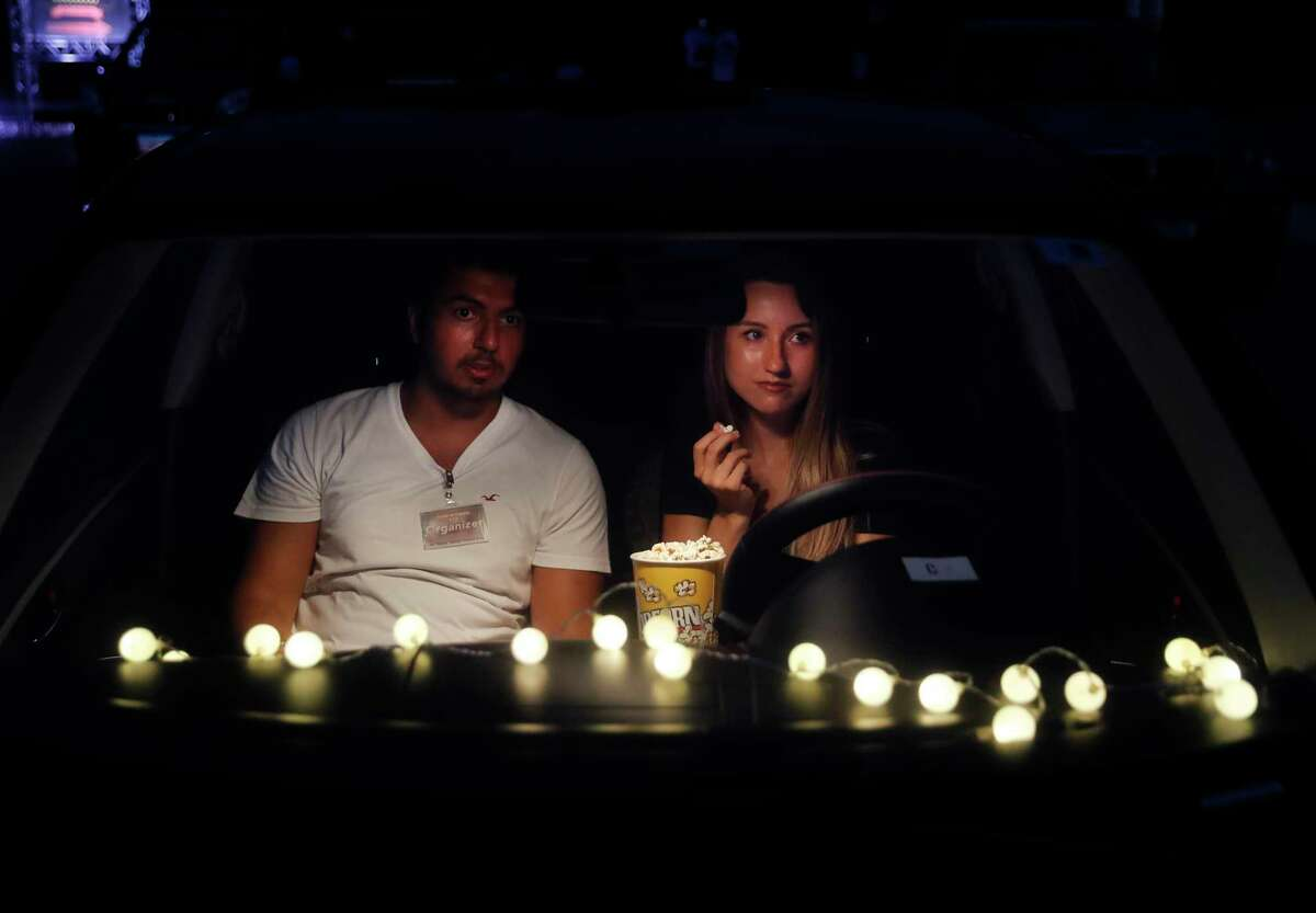 A couple sit on their car watch