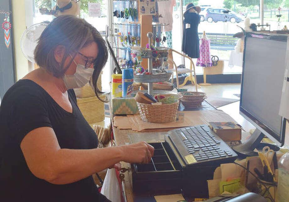 Rhonda Kircher, owner of Just Good Trade in Jacksonville, counts change from her register.