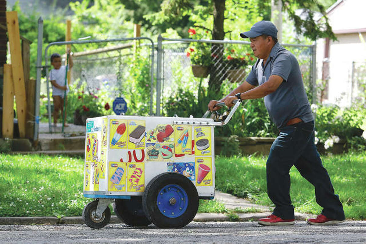 A child watches as paletero Pablo Perez pushes a cart full of Mexican ice cream bars and other frozen treats in Rockford.
