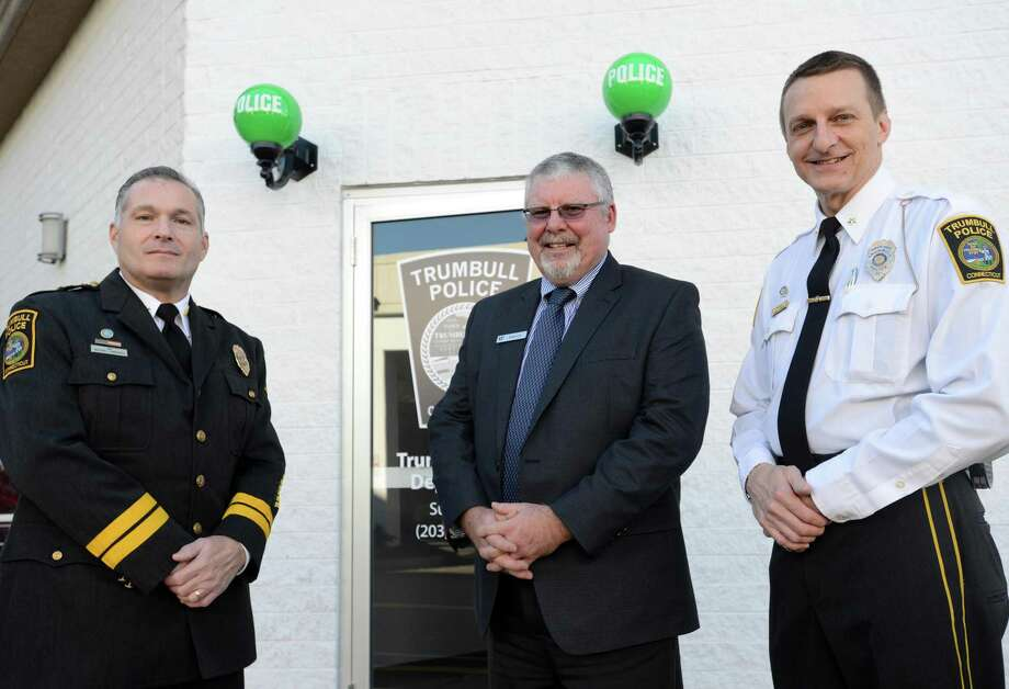Trumbull Police Chief Michael Lombardo, Westfield Trumbull Manager Patrick Madden and Deputy Chief Glenn Byrnes stand outside the new police substation at the Westfield Trumbull Mall on its first day open Tuesday, Nov. 17, 2015. Photo: Autumn Driscoll / Hearst Connecticut Media / Connecticut Post