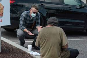 Justin Cullmer, New Milford Police community care coordinator, talks with a client in the parking lot of a local food business. Wednesday, July 15, 2020, in New Milford, Conn.