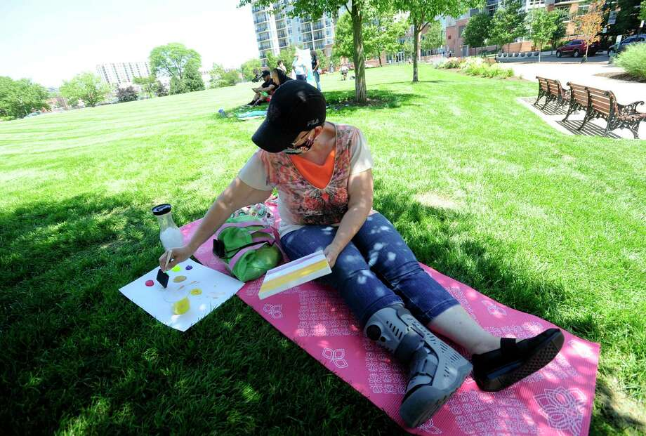 Elizabeth Rayo of Stamford finds a comfortable shady spot to create a painting as she participates in the Justice for Brunch Mental Wellness in the Black Community event at Harbor Point's Commons Park on July 18, 2020 in Stamford, Connecticut. Participants attending took part in guided meditation & breathwork, listened to the spoken word, speakers and music, got physical with a superhuman class and yoga and enjoyed stimulation in painting while enjoying the fresh air and shade of trees in the park. Photo: Matthew Brown / Hearst Connecticut Media / Stamford Advocate