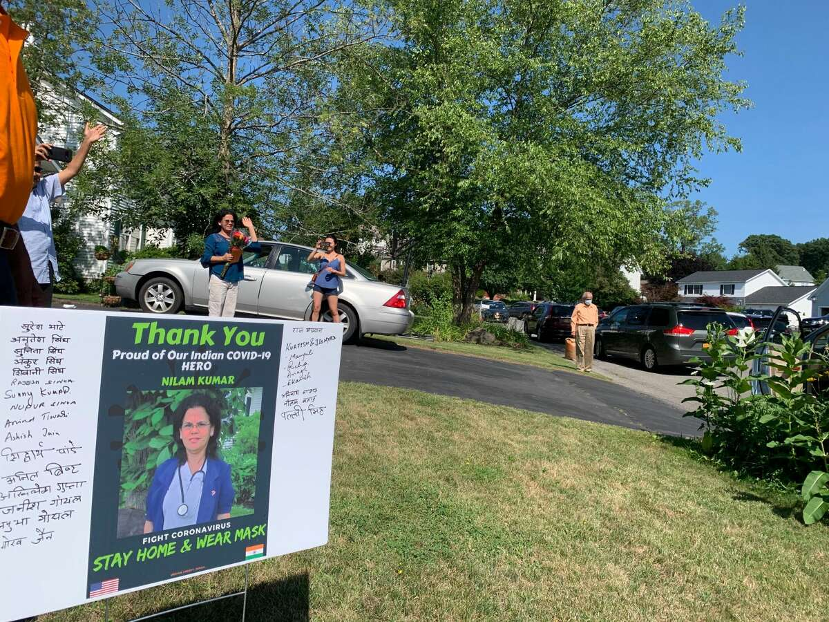 Dozens of cars, with drivers honking and passengers clapping, file past Nilam Kumar's Latham home on Saturday, July 18, 2020. The parade was planned by the North Indian Hindu Association of Albany to celebrate Kumar, who works as a LPN nurse at a Rensselaer County nursing home. Participants put a placard in Kumar's yard and gave her a bouquet of flowers.