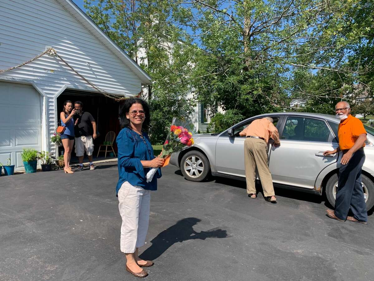 Dozens of cars, with drivers honking and passengers clapping, file past Nilam Kumar's Latham home on Saturday, July 18, 2020. The parade was planned by the North Indian Hindu Association of Albany to celebrate Kumar, who works as a LPN at a Rensselaer County nursing home. Participants put a placard in Kumar's yard and gave her a bouquet of flowers.