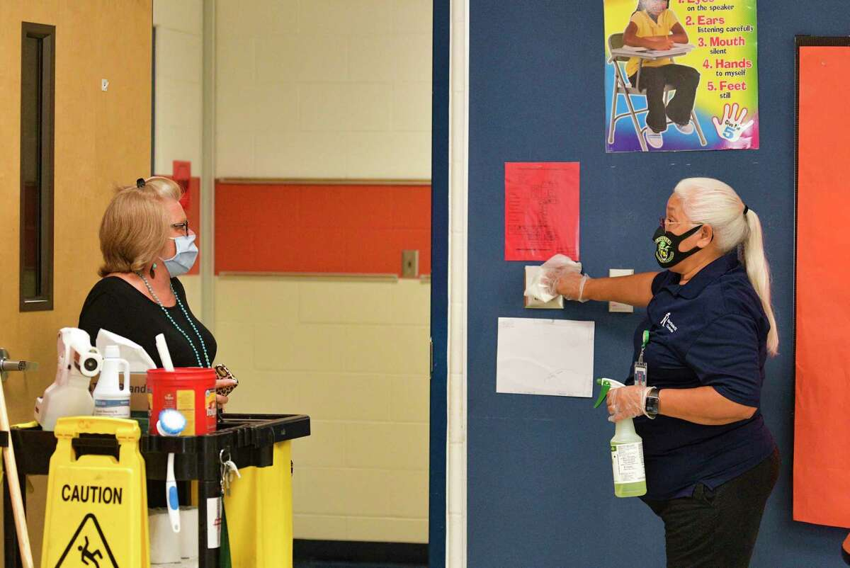 Maria Reyes, right, head custodian at the Northside ISD's Forester Elementary School, speaks with principal Kelly Mantle while cleaning light switches in a classroom last July.