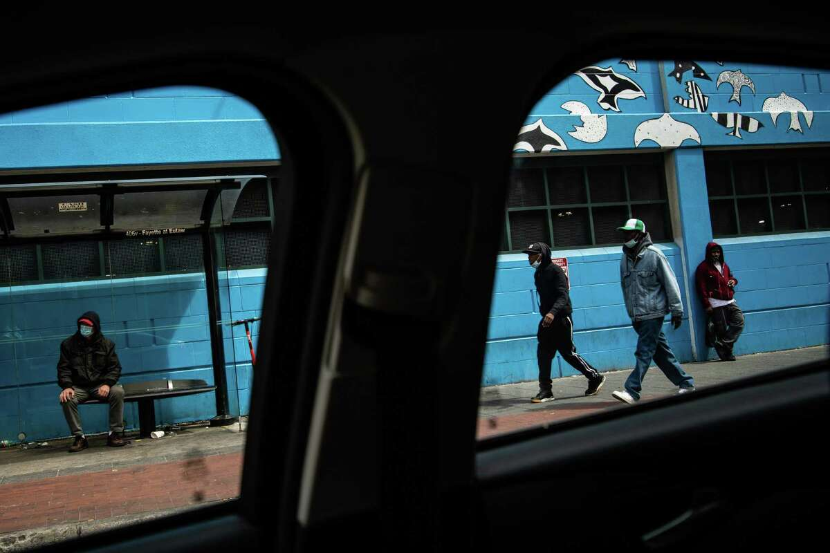 People wait at a bus stop near Lexington Market Station on May 21, 2020, in Baltimore.
