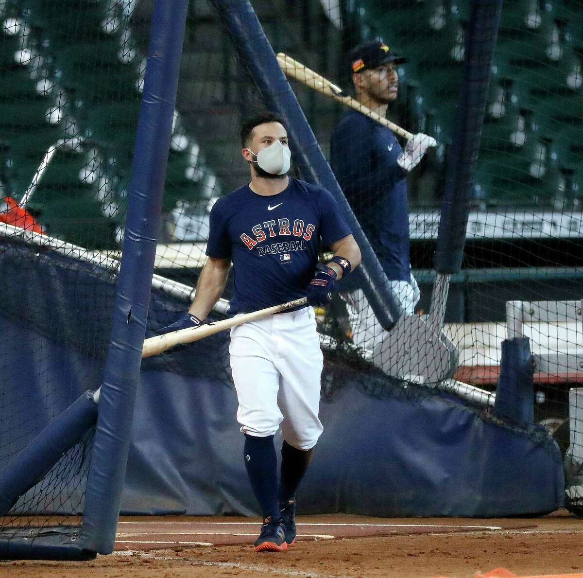 Houston Astros Jose Altuve wears a face mask as he took batting practice in the cage during the Astros summer camp at Minute Maid Park, Saturday, July 18, 2020, in Houston.