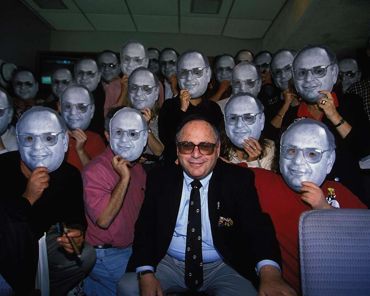 Hank Greenwald sits in the center of a group photo from his birthday party, surrounded by guests holding up cardboard cutouts of his face.