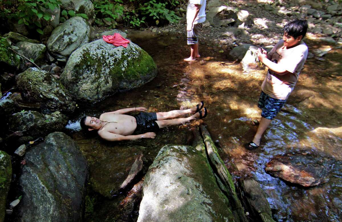 Jose Vazquez, 14, of Queens, NY, at right, snaps pictures of his dad Antonio Lopez laying in the water of the creek at Indian Well State Park in Shelton, Conn., on Saturday July 18, 2020.