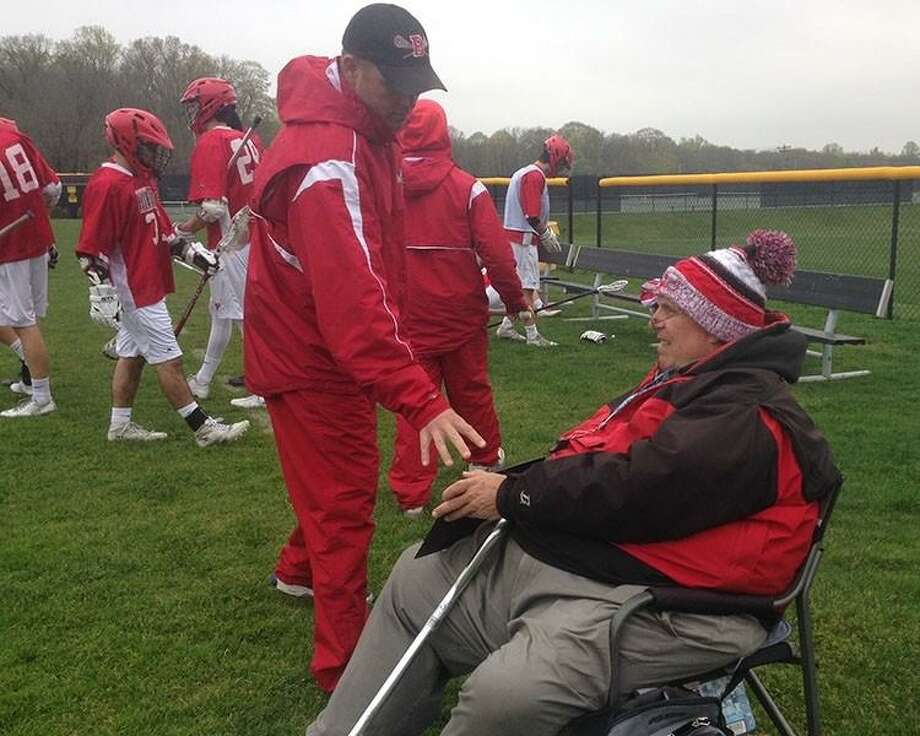 """Branford assistant boys lacrosse coach Frank Barron looks on as athletes and coaches go through the tradition of tapping a sign held by Barron that reads """"Expect To Win."""" Photo: Contributed Photo"""