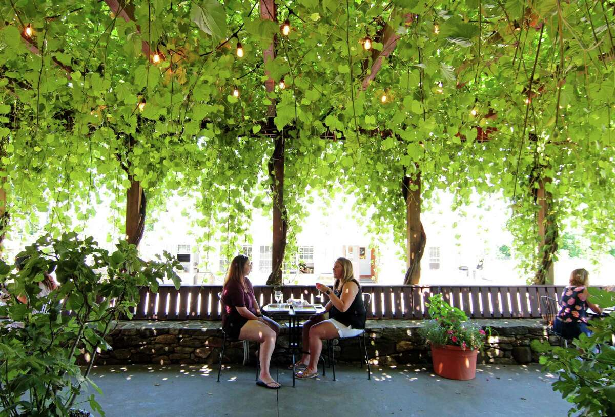 Tiffany DeMica, of Danbury, and her friend Kristen Commander, of Shelton, at right, enjoy wine on the shaded terrace at Jones Winery at Jones Family Farm in Shelton, Conn., on Saturday July 18, 2020.
