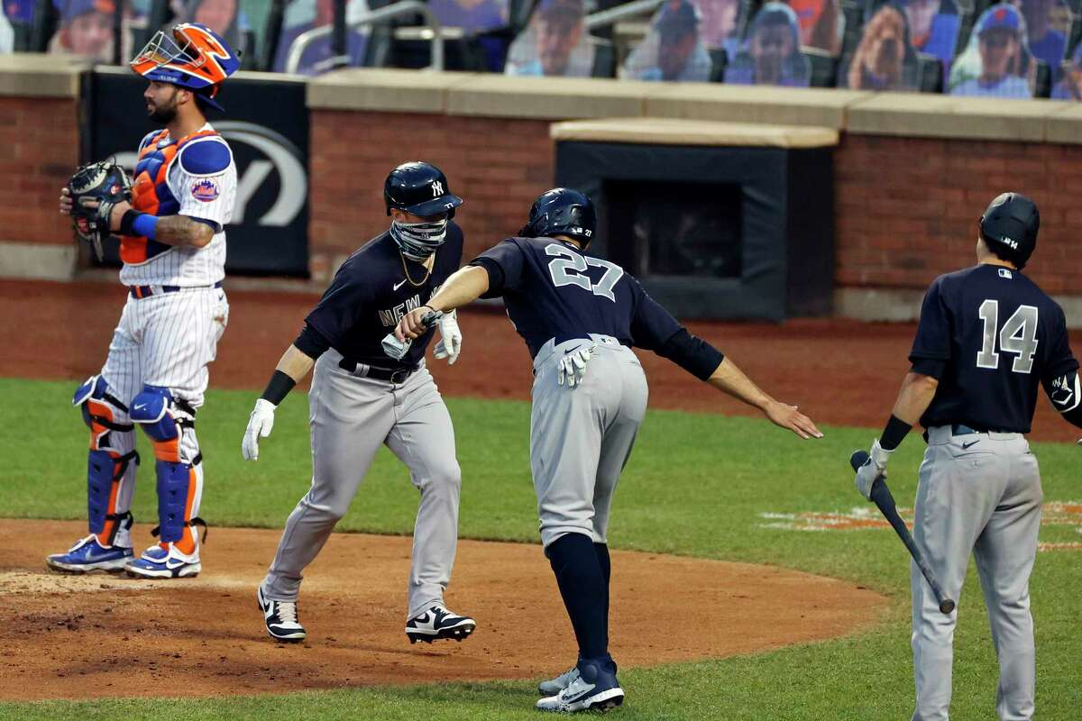 New York Yankees' Clint Frazier, second from left, is congratulated by designated hitter Giancarlo Stanton (27) after hitting a two-run home run against the New York Mets during the fourth inning of a spring training baseball game Saturday, July 18, 2020, in New York. (AP Photo/Adam Hunger)