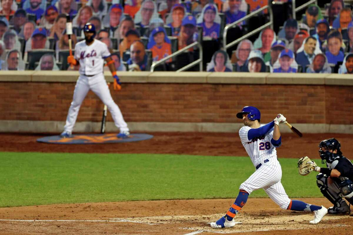New York Mets' J.D. Davis (28) follows through on an RBI-double against the New York Yankees during the fourth inning of a baseball spring training game Saturday, July 18, 2020, in New York. (AP Photo/Adam Hunger)