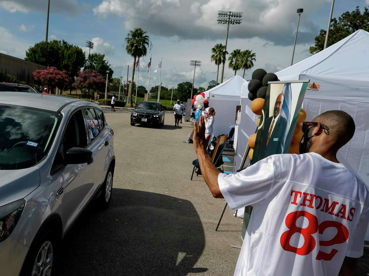 Warren Luckett, right, waves at a driver who attended the drive-through memorial service for former NFL wide receiver Earl Thomas, who played for the Bears, Cardinals and Oilers, outside the University of Houston Alumni Center on Saturday, July 18, 2020, in Houston. Thomas attended University of Houston, where he played college football. He later founded a refining company, developed low-income housing and became a nationally-recognized track and field coach.