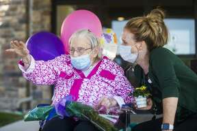 Betty Jo Browning waves to a friend as they drive by during a parade in celebration of Betty Jo's 99th birthday Friday, July 17, 2020 at Primrose Retirement Community of Midland. (Katy Kildee/kkildee@mdn.net)