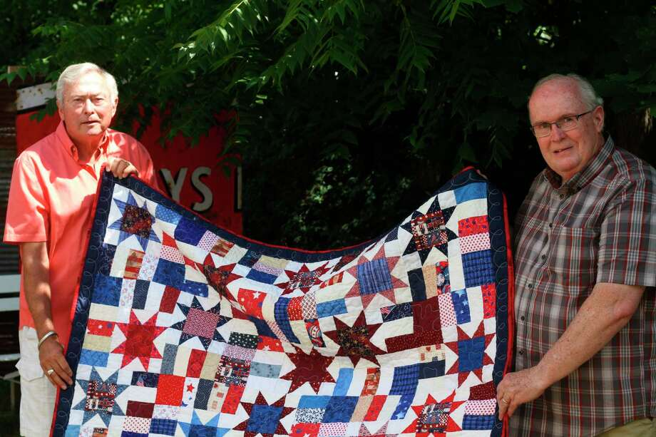 John Wemlinger (left) receives a Quilt of Valor from Bert Murphy (right) during a small ceremony at the Yellow Dog Cafe in Onekama on Friday. (Kyle Kotecki/News Advocate)