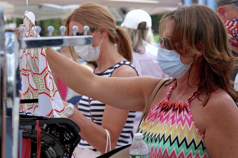 Maria Cimino of Fairfield looks over some merch at the annual Sidewalk Sale & Street Fair on Saturday, July 18, 2020, in Fairfield, Conn. Photo: Jarret Liotta / Jarret Liotta / ©Jarret Liotta 2020