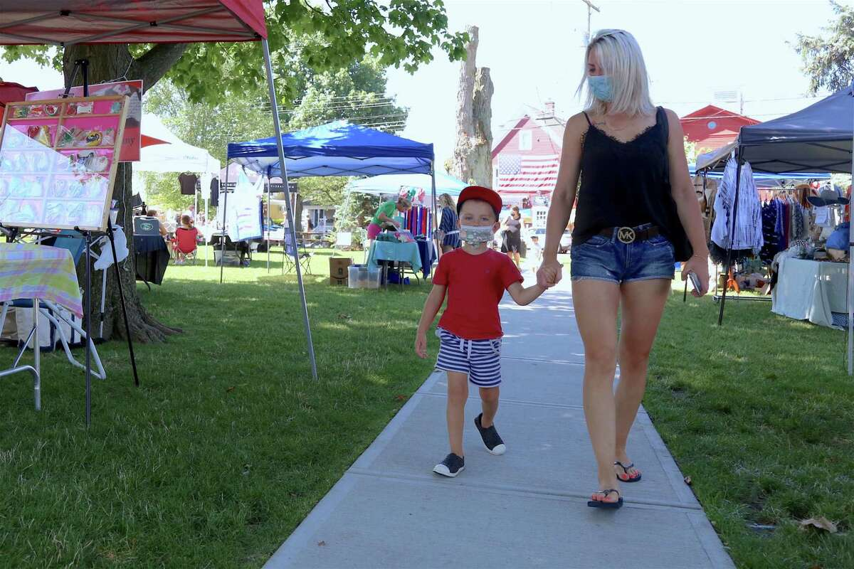 Joanna Soltys of Shelton and her son Arthur, 3, check out the booths on Sherman Green at the annual Sidewalk Sale & Street Fair on Saturday, July 18, 2020, in Fairfield, Conn.