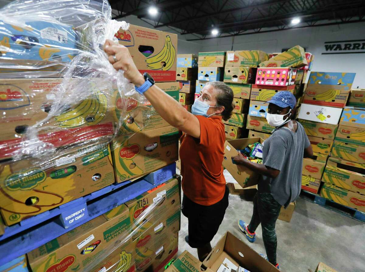 Volunteer Suzanne Hollifield unwraps a pallet of produce to sort for clients at Saint Isidore Episcopal Church's event space, in Spring. The non-profit recently began utilizing its kitchen and food pantry to help the community amid the coronavirus pandemic after renovating the 8,000 square-foot building.