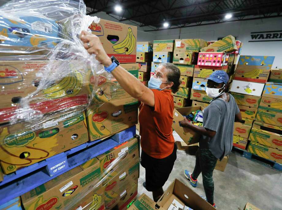 Volunteer Suzanne Hollifield unwraps a pallet of produce to sort for clients at Saint Isidore Episcopal Church's event space, in Spring. The non-profit recently began utilizing its kitchen and food pantry to help the community amid the coronavirus pandemic after renovating the 8,000 square-foot building. Photo: Jason Fochtman, Houston Chronicle / Staff Photographer / 2020 © Houston Chronicle