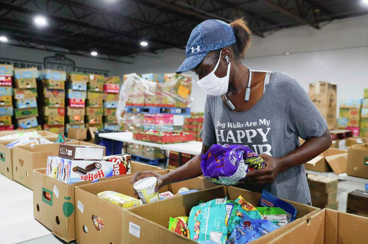 Volunteer Ka Janna Williams sorts through items for a client at Saint Isidore Episcopal Church's event space in Spring. The non-profit recently began utilizing its kitchen and food pantry to help the community amid the coronavirus pandemic after renovating the 8,000 square-foot building.