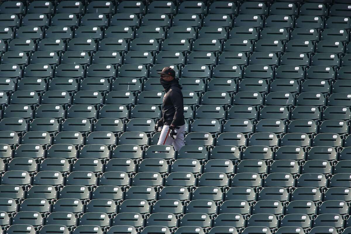 A person wearing San Francisco Giants clothing walks through the empty stands during an inter squad game at Oracle Park on Wednesday, July 15, 2020 in San Francisco, Calif.