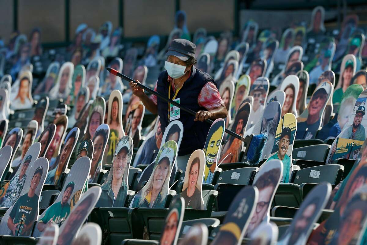 Martha Arreola cleans seats occupied with cardboard cutouts of fans during the Oakland A's summer training camp at the Coliseum in Oakland, Calif. on Saturday, July 18, 2020.
