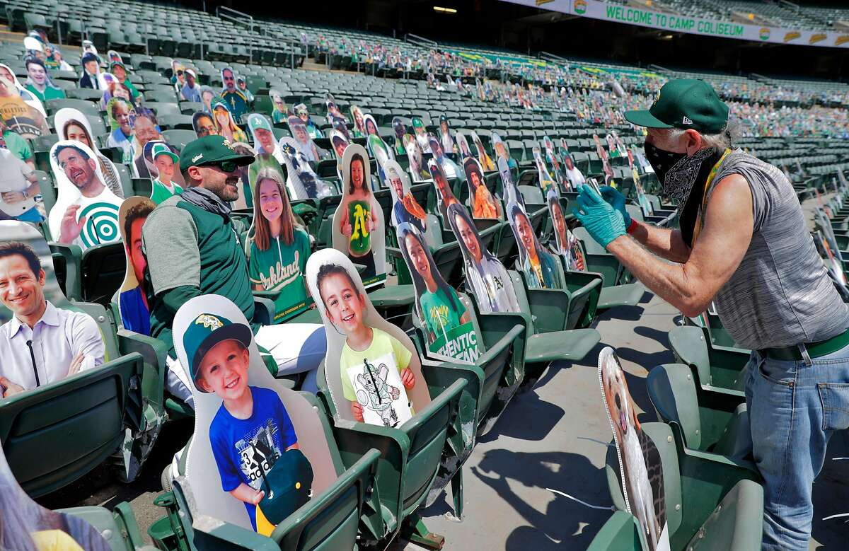 A's team photographer Mike Zagaris takes a photo of A's bench coach Ryan Christenson with a cutout of his daughter in the stands as the Oakland Athletics played in a simulated game at the Coliseum in Oakland, Calif., on Sunday, July 19, 2020.