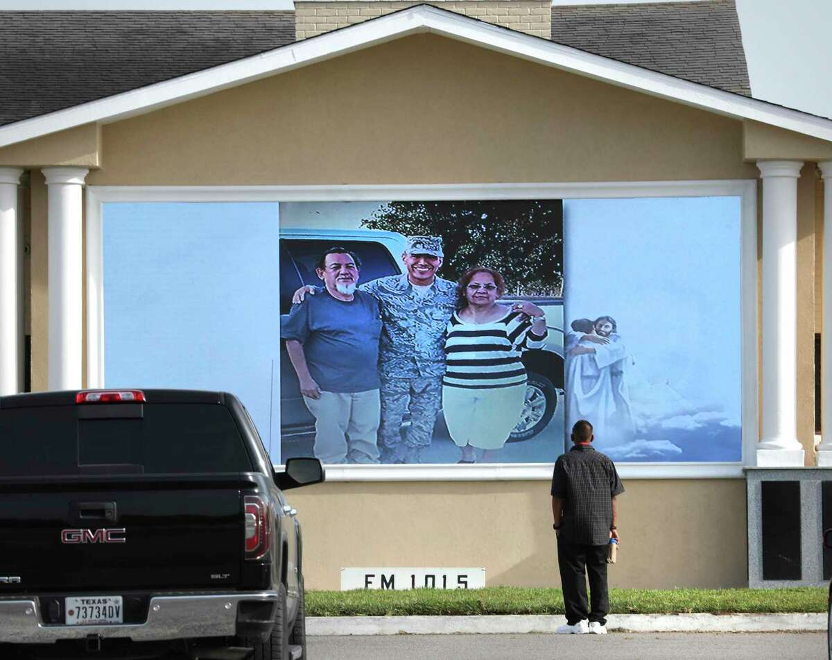 A friend of Tomas Morales stands in front of large outdoor TV screens to watch the memorial slideshow for Morales on Friday, July, 17, 2020, at Mission Park Funeral Chapels South. Funeral homes are seeing more business as the number of people dying because of the coronavirus has surged since June.