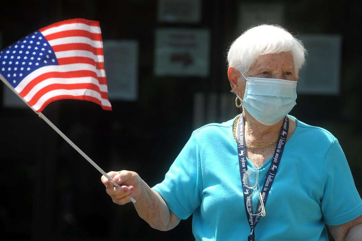 Hollander House resident Theresa Giunta waves an American flag as she watches an Independence Day drive-by parade in Bridgeport, Conn. July 2, 2020. Volunteers drove through the Jewish Senior Services and Hollander House campus Thursday to help the residents celebrate the upcoming Fourth of July weekend.