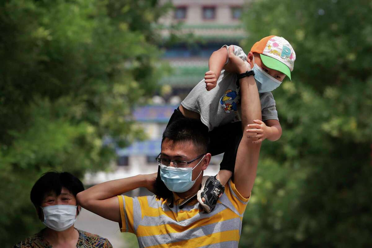 A man wearing a face mask to protect against the new coronavirus puts his masked child on his shoulders as they visit to a shopping district in Beijing, Sunday, July 19, 2020. China on Sunday reported another few dozen of confirmed cases of the coronavirus in the northwestern city of Urumqi, raising the total in the country's most recent local outbreak to at least 30. (AP Photo/Andy Wong)