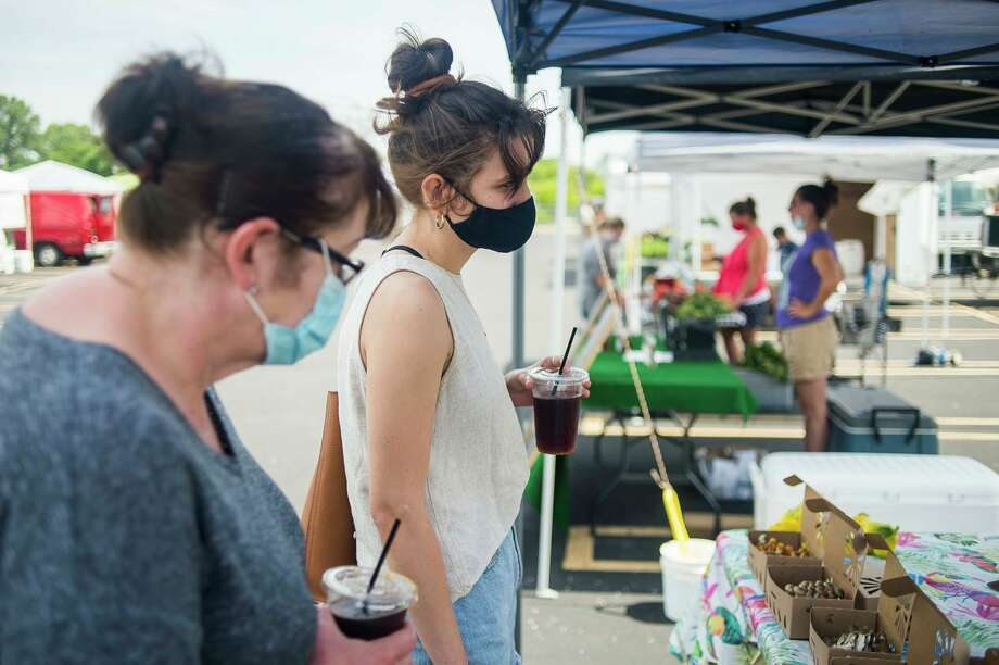 Midland residents peruse stalls at the Midland Area Farmers Market, at its temporary location in the parking lot next to Dow Diamond July 15, 2020. (Daily News file photo/Katy Kildee/kkildee@mdn.net)