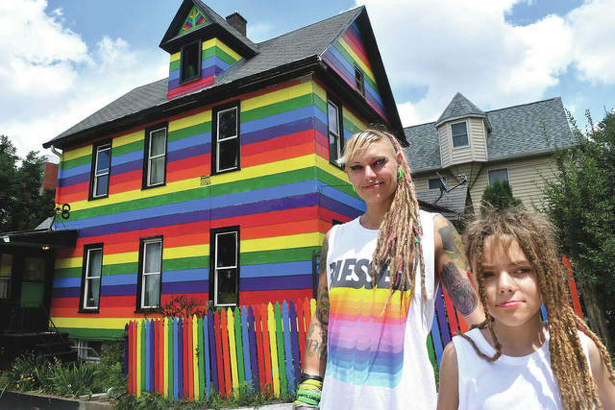 Taylor Berg and her son, Mattix, 10, stand in front of their house in Moline. City officials said Berg does not have to paint over the broad purple, blue, green, yellow, orange and red horizontal stripes that run top to bottom down her two-story wood-frame house.