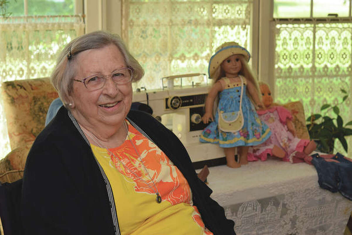 """Dixie Thompson with her """"200,000-mile"""" sewing machine and some doll clothes she has made."""