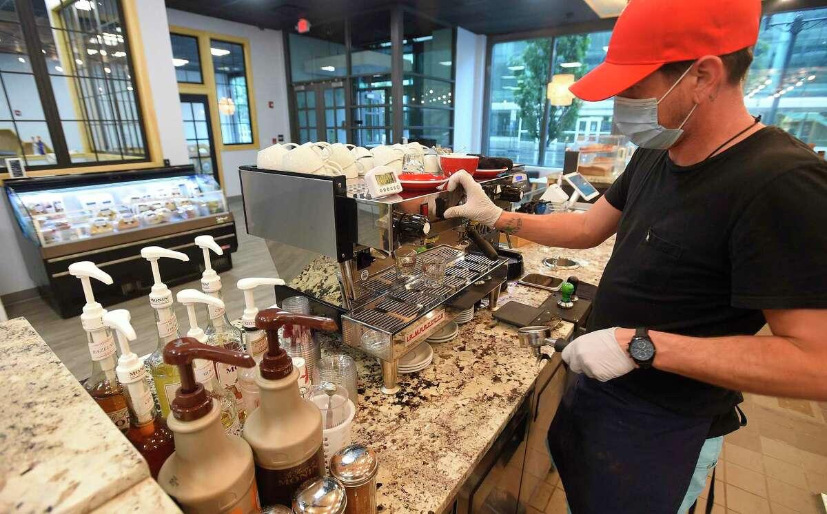 Barista Josh Smith make a signature house latte at Honey Joe's Family Coffeehouse on July 10, 2020.