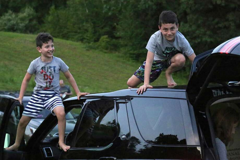 "Benjamin Zev, 7, left, of Weston, and his brother Eli, 10, do some climbing at the Lachat Town Farm pop-up drive-in movie screening of ""Caddyshack"" on Sunday, July 19, 2020, in Weston, Conn. Photo: Jarret Liotta / Jarret Liotta / ©Jarret Liotta 2020"