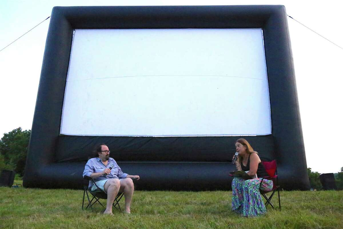 """Carol Baldwin, documentarian and chair of the Friends of Lachat, interviews author Chris Nashawaty of Westport at the Lachat Town Farm pop-up drive-in movie screening of """"Caddyshack"""" on Sunday, July 19, 2020, in Weston, Conn."""