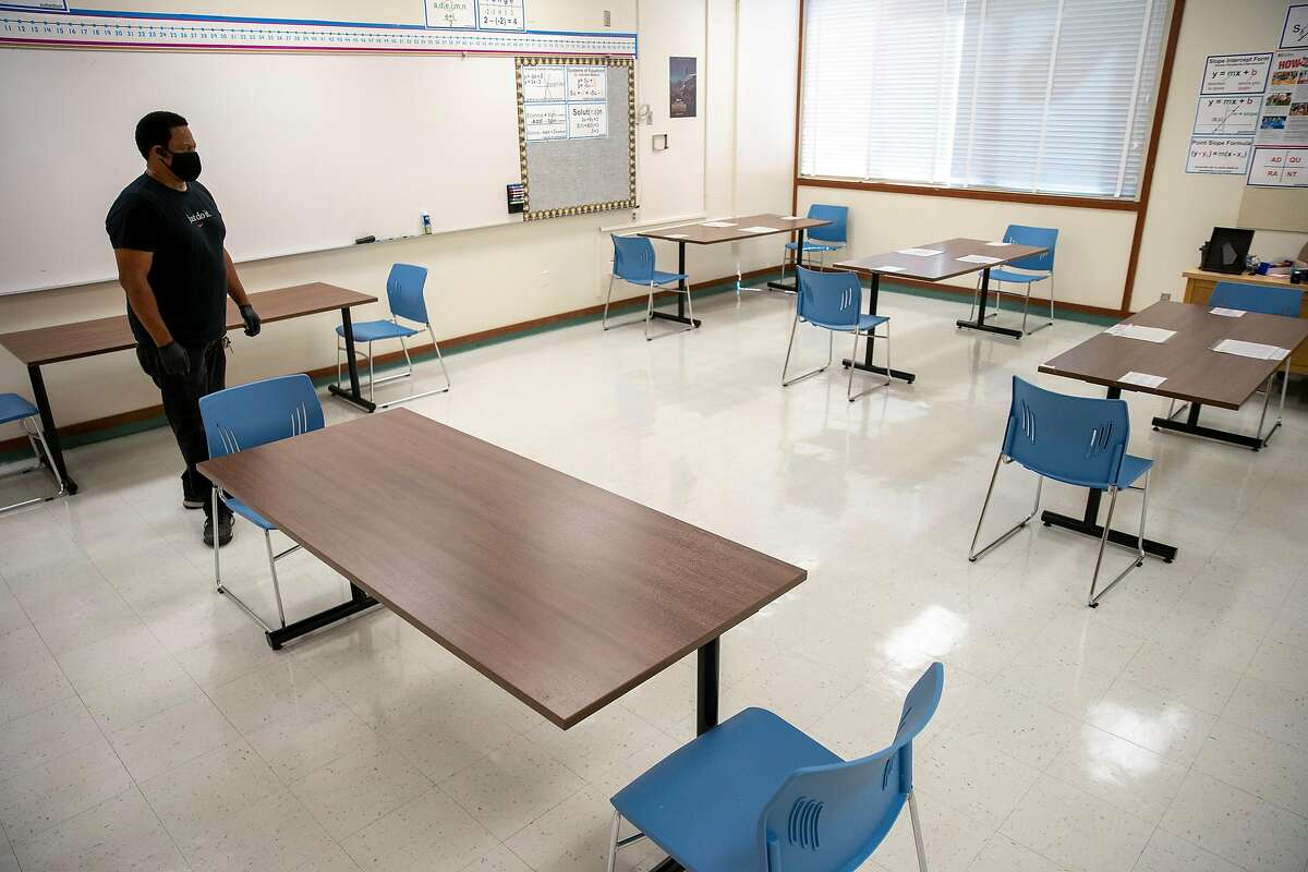 Philip Elliott, the supervising custodian, checks one of the classrooms that's set up for physical distancing at Westlake Middle School on Friday, July 10, 2020, in Oakland, Calif.