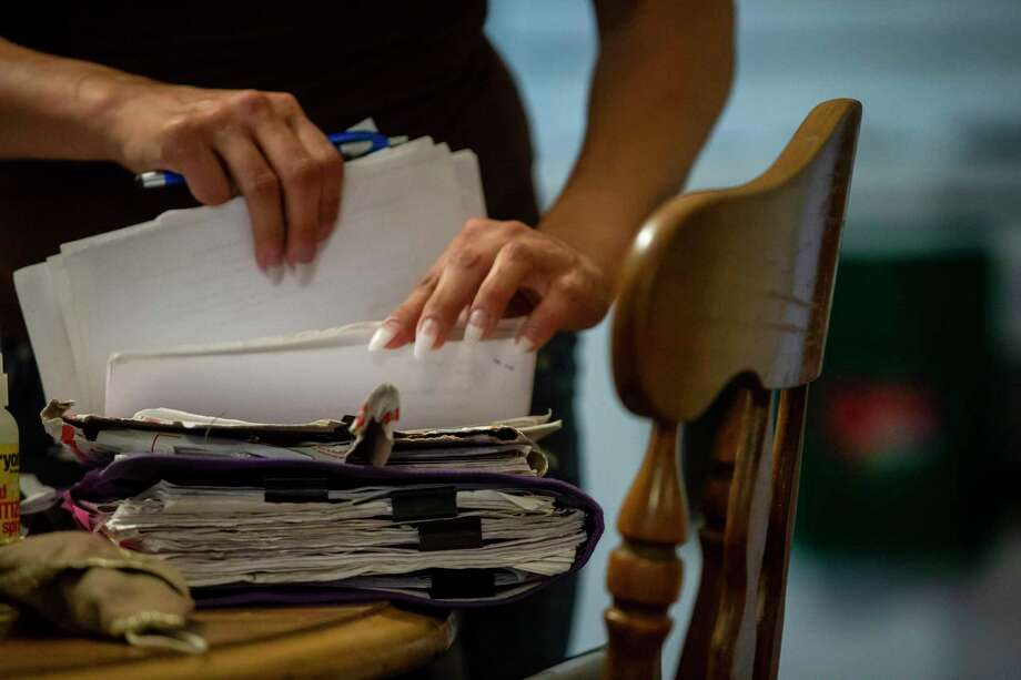 A 51-year-old victim of now-disbarred Mark Benavides goes through paperwork at her San Antonio home on June 18, 2020. She was arrested in 2013 for DWI; he insisted she plead guilty even though she said she was innocent. A recent review off the case showed the arrest wasn't supported by evidence and her conviction has been overturned based on Benavides' ineffectual counsel. Photo: Josie Norris /Staff Photographer / **MANDATORY CREDIT FOR PHOTOG AND SAN ANTONIO EXPRESS-NEWS/NO SALES/MAGS OUT/TV