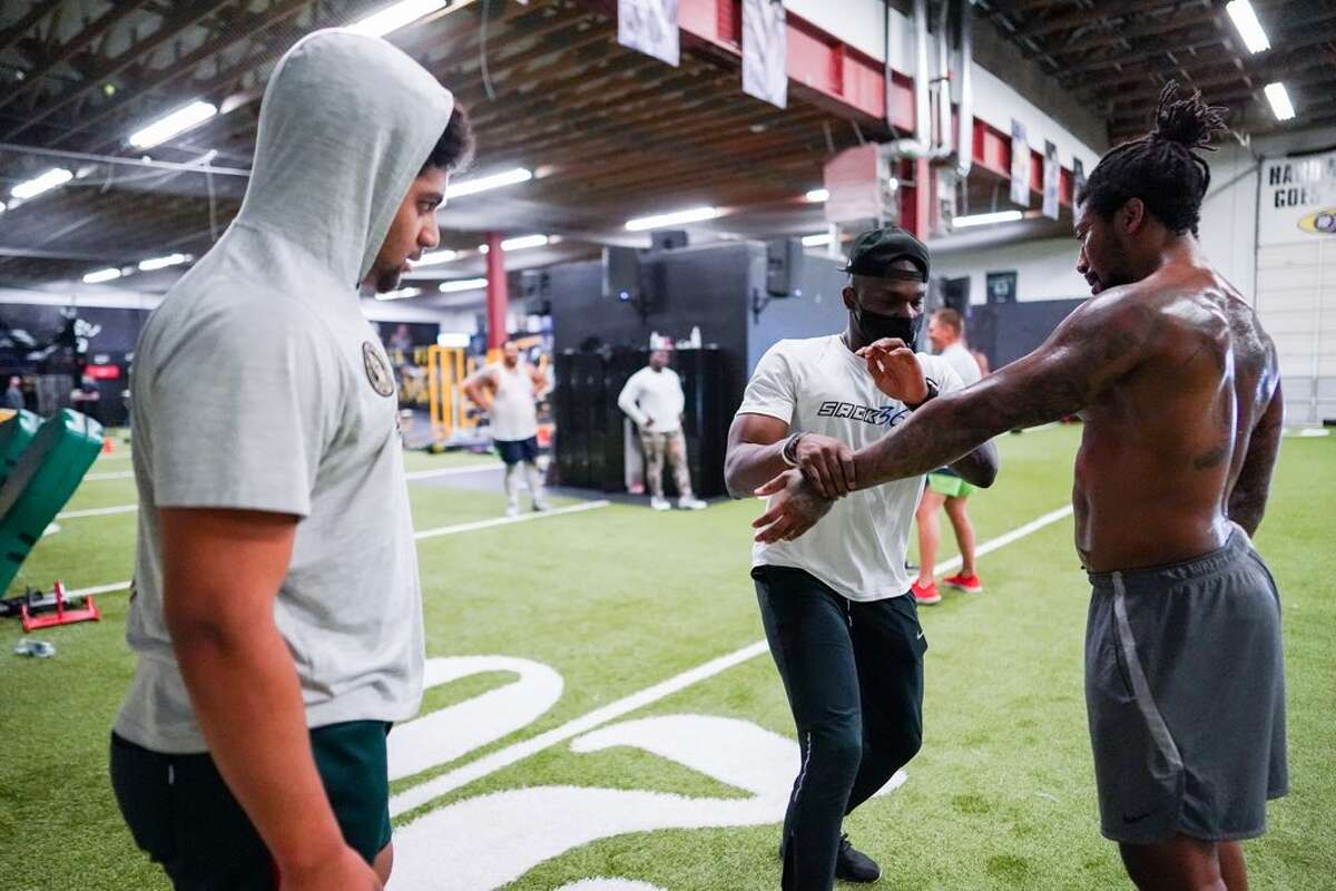 Former Seahawks star Cliff Avril (middle) working with Seahawks defensive end/outside linebacker Bruce Irvin (right) and Eastside Catholic standout Jaylahn Tuimoloau at his pass-rush academy.