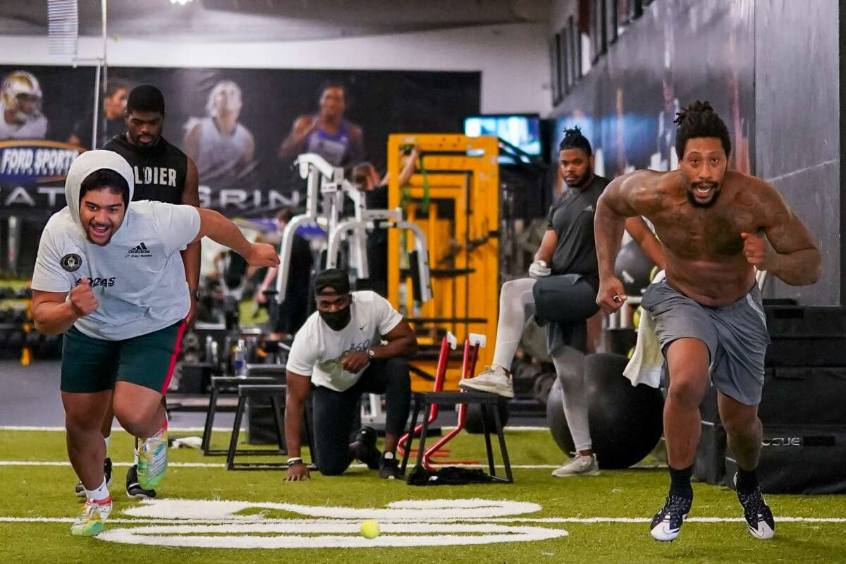 Former Seahawks star Cliff Avril (middle) watches as the Seahawks' Bruce Irvin (right) and top-ranked Eastside Catholic star Jaylahn Tuimoloau do a pass-rush drill.