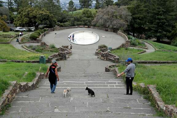 Park visitors keep their distance while their pups try to get closer as sparse crowds showed up at Joaquin Miller Park as people get out of their homes during the statewide shelter in place in Oakland, Calif., on Sunday, March 22, 2020.
