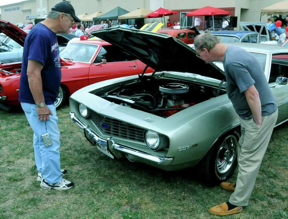 SPECTRUM/People flocked from all over to attend the fourth annual Cruzin New Milford 2010 car and motorcycle night, Aug. 15, 2010 at Faith Church in New Milford. Here, Korean War veteran Larry Terhune, left, and Vietnam War veteran John Gully, both from New Milford, take a look under the hood of a 1969 Camero.