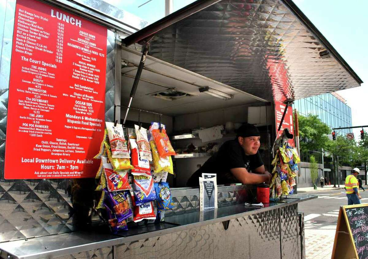 Joe Marzan tends the Snappy Dogs food cart recently outside the State Courthouse on the corner of Fairfield Avenue and Main Street in Bridgeport. Marzan runs the cart with his mother Janet Marzan.