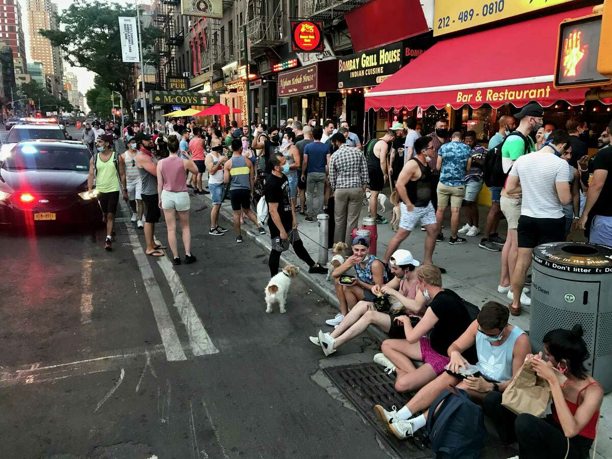 FILE -- People congregate in violation of social distancing rules in the Hell's Kitchen neighborhood of Manhattan, June 13, 2020 New York's restaurants and bars, struggling to stay afloat with skeleton staffs and reduced to takeout, delivery and outdoor dining, suffered another blow on July 16 when Gov. Andrew Cuomo placed new limits on their ability to serve alcohol.