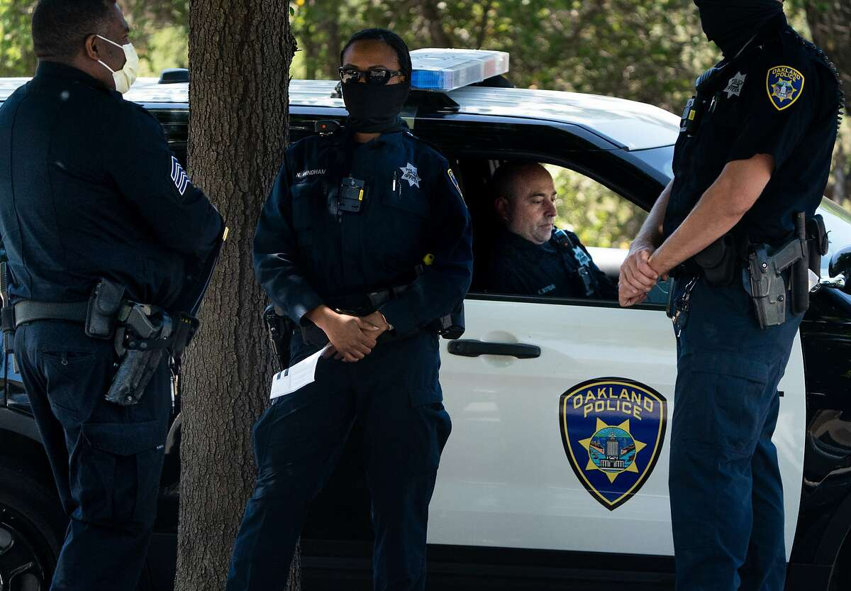 OPD officers from left: Sgt. Burke, Natalie Windham, Kris Botelho and Officer Joel Warford at Mountain Blvd. in Montclair Village on Tuesday, June 30, 2020 in Oakland, Calif.. The Oakland City Council is meeting today to consider further cuts from the police department's budget.