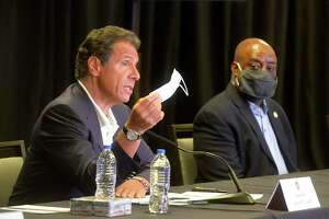 New York Gov. Andrew Cuomo waves a mask to make a point during a news conference at the Hyatt, in Savannah, Ga. on Monday, July 20, 2020. Listening in is Savannah Mayor Van Johnson.